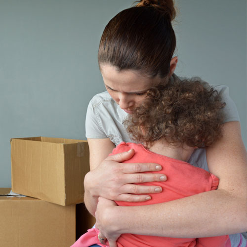 Woman holding crying child with moving boxes scattered around